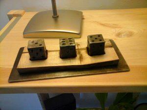3 dés forgés, sur plaquette de pistachier et tôle d'acier.